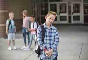 Sad boy in front of school
