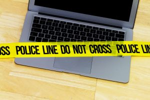 Image of police crime scene tape over a laptop