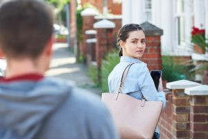 young woman texting on mobile phone for help while being stalked