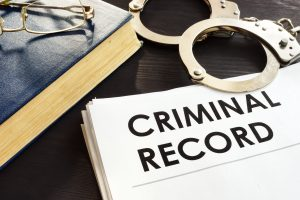 Criminal Record file next to handcuffs
