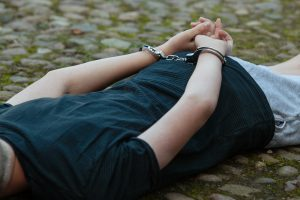 Teenager laying on ground after being arrested
